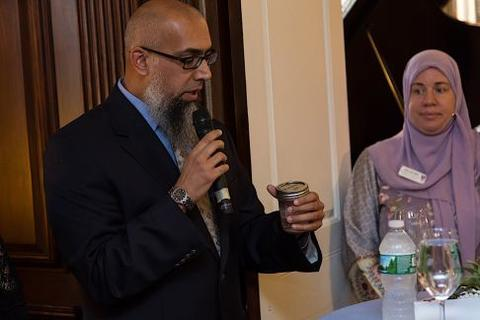 Omer Bajwa delivers blessing as wife Lisa looks on at Hawa Abdi Chubb Fellowship reception